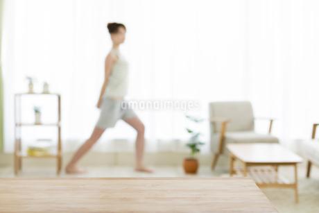 テーブルとストレッチをする女性の写真素材 [FYI01621661]