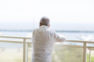 バルコニーで景色を眺めるシニア男性の写真素材 [FYI01621667]
