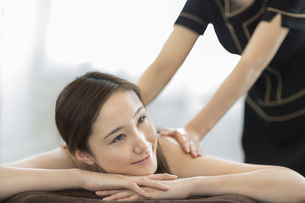 背中のオイルマッサージを受ける若い女性の写真素材 [FYI01621675]