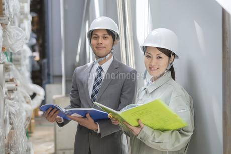 ファイルを持ち調べる男女の社員の写真素材 [FYI01621681]