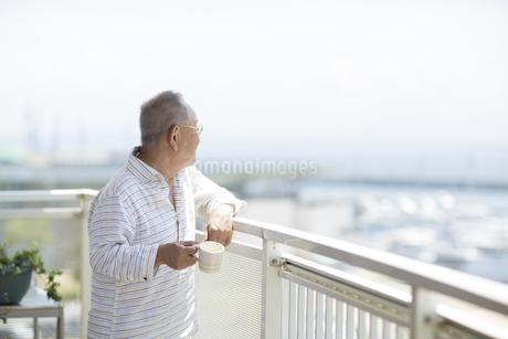 バルコニーで景色を眺めるシニア男性の写真素材 [FYI01621684]