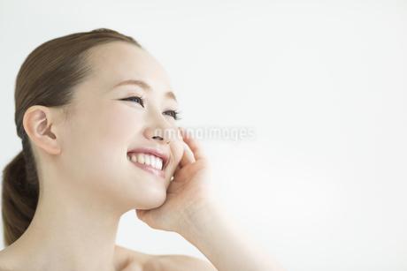 頬に手をあてる女性のスキンケアイメージの写真素材 [FYI01621698]