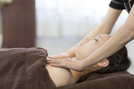 デコルテのオイルマッサージを受ける若い女性の写真素材 [FYI01621699]