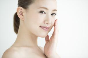 頬に手をあてる女性のスキンケアイメージの写真素材 [FYI01621704]