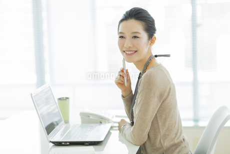机に座る笑顔のビジネスウーマンの写真素材 [FYI01621706]