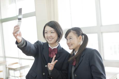携帯電話で撮影する笑顔の女子校生の写真素材 [FYI01621710]