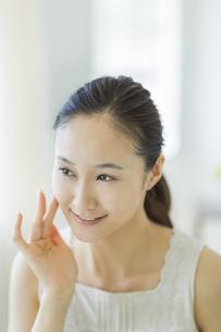 指で頬に触れ潤いを実感し微笑むスキンケアイメージの写真素材 [FYI01621712]