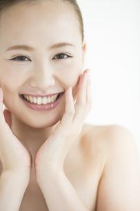 頬に手をあてる女性のスキンケアイメージの写真素材 [FYI01621729]