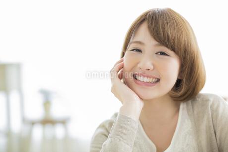 頬杖をつく笑顔の若い女性の写真素材 [FYI01621731]