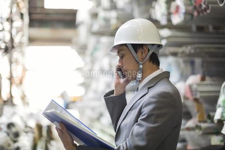 ファイルを持ち通話する男性社員の写真素材 [FYI01621737]