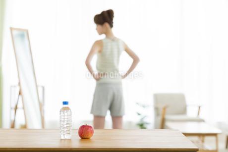 テーブルの上のリンゴと水と鏡を見る女性の写真素材 [FYI01621750]