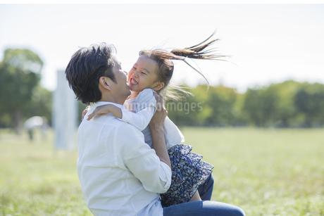 父親に駆け寄り抱きつく女の子の写真素材 [FYI01621756]
