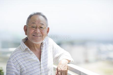 バルコニーで笑顔のシニア男性の写真素材 [FYI01621760]