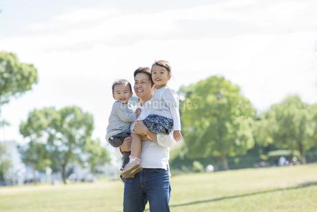 2人の子供を抱っこして笑顔の父親の写真素材 [FYI01621764]