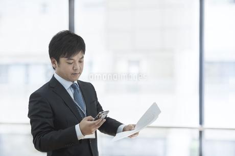 書類を持ち通話するビジネスマンの写真素材 [FYI01621811]