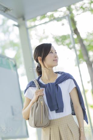 バス停に立つ出勤中のビジネスウーマンの写真素材 [FYI01621814]