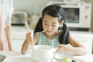 キッチンでお手伝いをする女の子の写真素材 [FYI01621824]