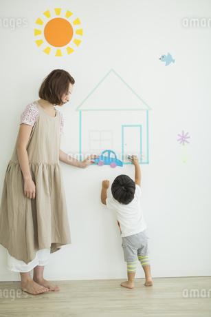 壁のイラストの前で遊ぶ親子の写真素材 [FYI01621834]