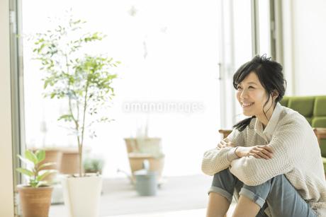 床に座る笑顔の女性の写真素材 [FYI01621839]