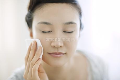コットンを顔にあてるスキンケアイメージの写真素材 [FYI01621840]