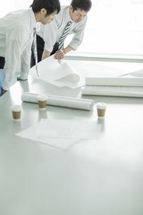 テーブルに図面を広げて打ち合わせをするビジネスマンの写真素材 [FYI01621841]