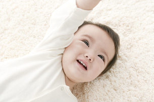 寝転び手を伸ばす赤ちゃんの写真素材 [FYI01621845]