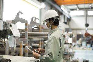 タブレットPCを操作する作業服の男性の写真素材 [FYI01621848]