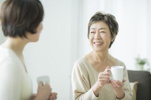 お茶を飲みながら笑顔で会話をする母娘の写真素材 [FYI01621851]