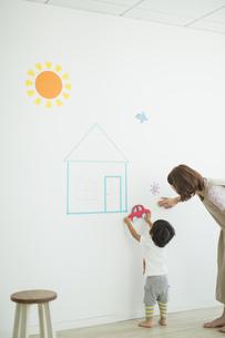 壁のイラストの前で遊ぶ親子の写真素材 [FYI01621859]