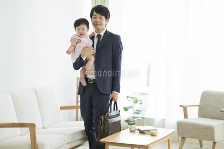 赤ちゃんを抱っこして出勤をする父親の写真素材 [FYI01621863]
