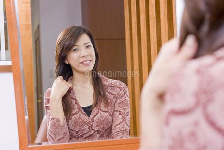 美容室の鏡に映る笑顔の40代女性の写真素材 [FYI01621876]
