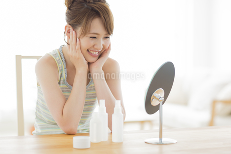 頬に両手をあてて鏡を見る女性の写真素材 [FYI01621884]