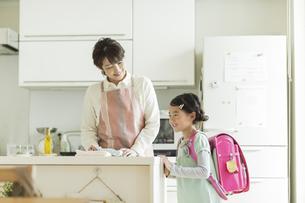 キッチンに立つ母親とランドセルを背負った女の子の写真素材 [FYI01621887]