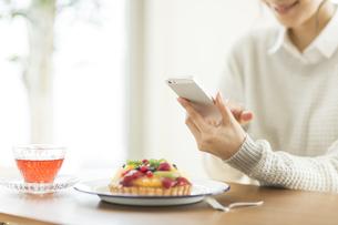 携帯電話でケーキを撮る女性の写真素材 [FYI01621894]