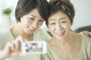 スマートフォンで写真を撮る母娘の写真素材 [FYI01621899]