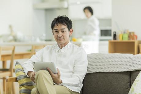 タブレットPCを持って笑顔の男性の写真素材 [FYI01621900]