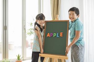 アルファベットを並べた黒板の横に立つ兄と妹の写真素材 [FYI01621924]