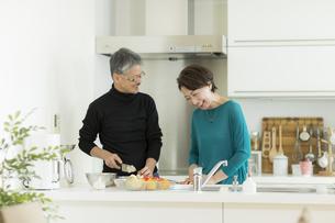 キッチンで調理をするシニア夫婦の写真素材 [FYI01621925]