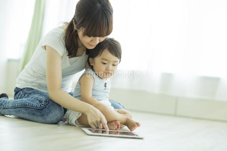 母親とタブレットPCで遊ぶ赤ちゃんの写真素材 [FYI01621937]