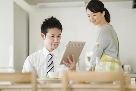 朝食中にタブレットPCを見る夫婦の写真素材 [FYI01621943]