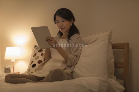 ベッドの上でタブレットPCを操作する女性の写真素材 [FYI01621971]