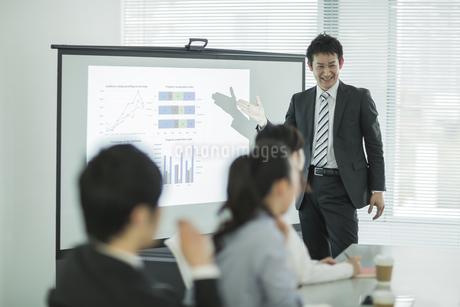 プロジェクターを使用した会議で説明をするビジネスマンの写真素材 [FYI01621972]