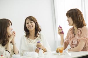 テータイムで楽しく会話する3人の若い女性の写真素材 [FYI01621980]