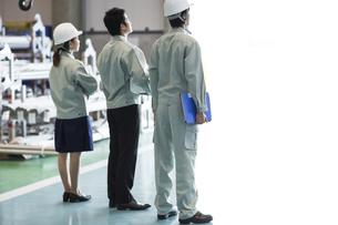 工場で上を見上げる男女の作業員の写真素材 [FYI01621981]