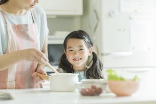 キッチンで料理をする母親に寄り添う女の子の写真素材 [FYI01621989]