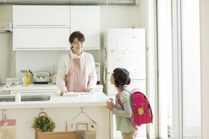 キッチンに立つ母親とランドセルを背負った女の子の写真素材 [FYI01621993]