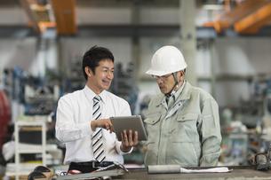 タブレットPCを見ながら打ち合わせをする作業員とビジネスマンの写真素材 [FYI01621995]