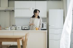 キッチンでコーヒーをカップに注ぐ女性の写真素材 [FYI01621999]