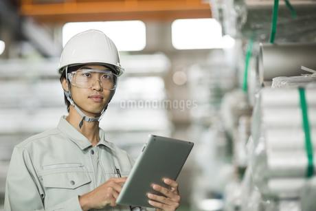 タブレットPCを操作する作業服の男性の写真素材 [FYI01622000]