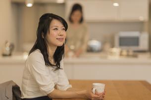 ダイニングテーブルでお茶を飲む娘の写真素材 [FYI01622006]